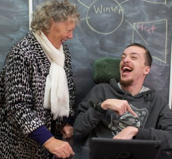 Young man in a wheelchair with his teacher
